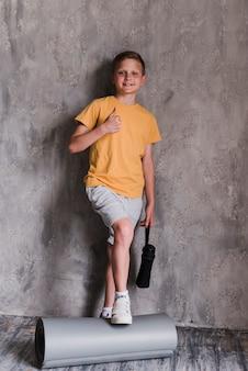 Glimlachende jongen die zich voor concrete muur bevindt die duimen toont