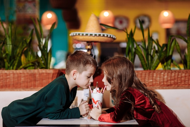 Glimlachende jongen en meisje die met twee rietjes drinken