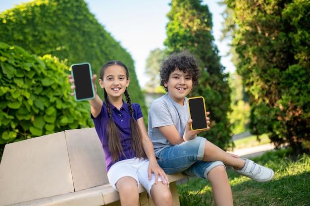 Glimlachende jongen en meisje die smartphones tonen