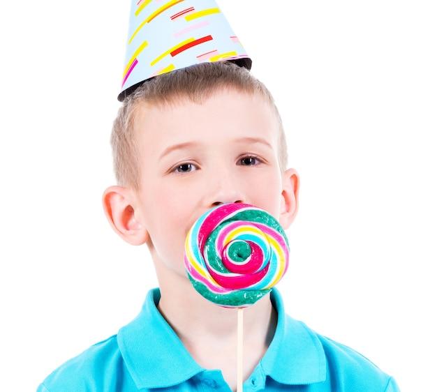 Glimlachende jongen in blauw t-shirt en feestmuts met gekleurd suikergoed - dat op wit wordt geïsoleerd.