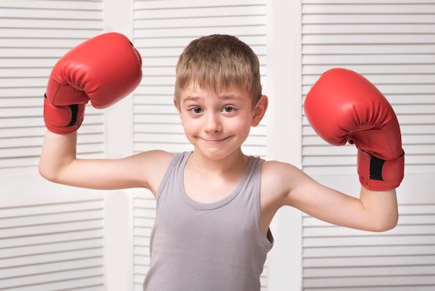 Glimlachende jongen in bokshandschoenen.