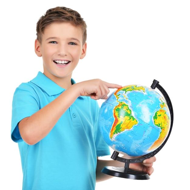 Glimlachende jongen in casual bedrijf wereldbol met in handen en punten op het geïsoleerd op wit