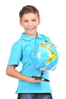 Glimlachende jongen in toevallige holdingsbol in handen die op wit worden geïsoleerd
