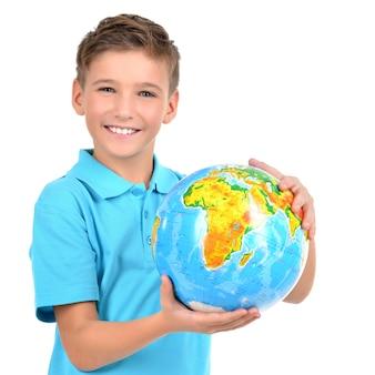 Glimlachende jongen in toevallige holdingsbol in handen - die op wit wordt geïsoleerd