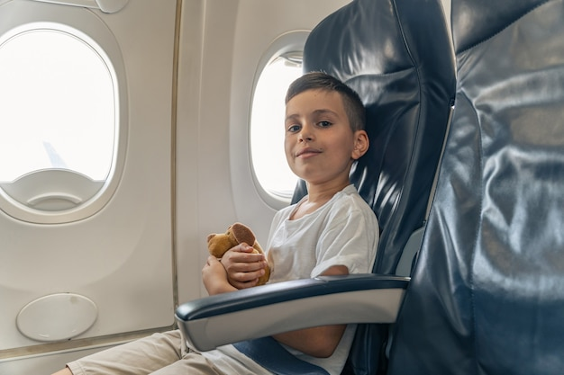 Glimlachende jongen in vliegtuig zittend op stoel bij raam