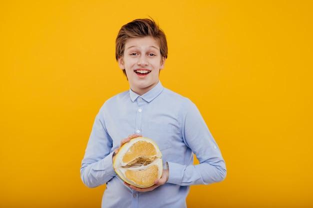 Glimlachende jongen met pompelmoesfruit in hand, in het blauwe die overhemd, op gele muur wordt geïsoleerd
