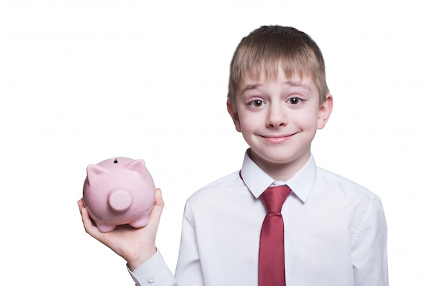 Glimlachende jongen met roze spaarvarken in zijn handen. bedrijfsconcept ... isoleren