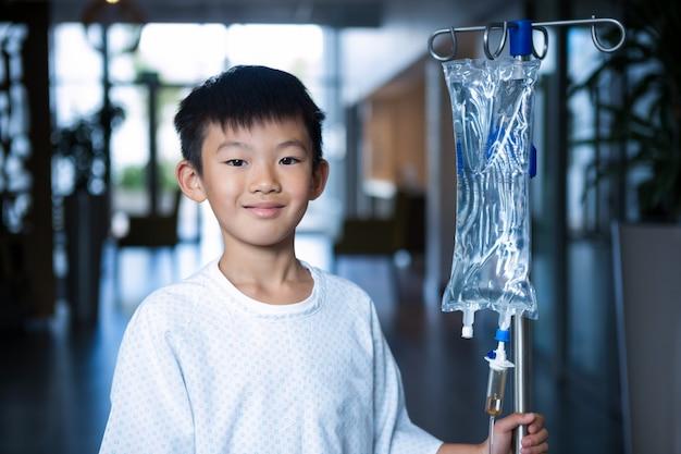Glimlachende jongen patiënt met intraveneuze iv infuusstandaard in gang