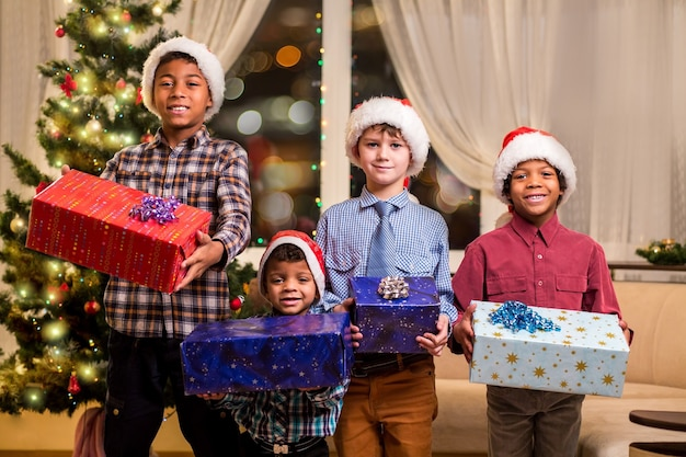 Glimlachende jongens die kerstcadeautjes houden. kinderen met cadeautjes naast sparren. vrolijke vakantiesfeer in huis. laat de goede tijden rollen.