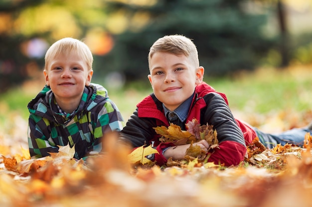 Glimlachende jongens op de grond met herfstbladeren