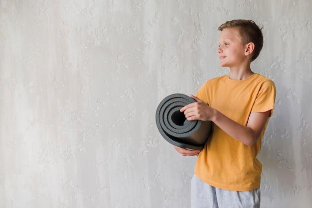 Glimlachende jongensholding opgerolde oefeningsmat die weg voor concrete muur kijken