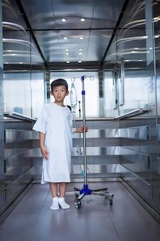 Glimlachende jongenspatiënt die intraveneuze iv infuusstandaard in lift houden