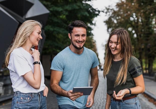Glimlachende jongeren die in een tablet kijken