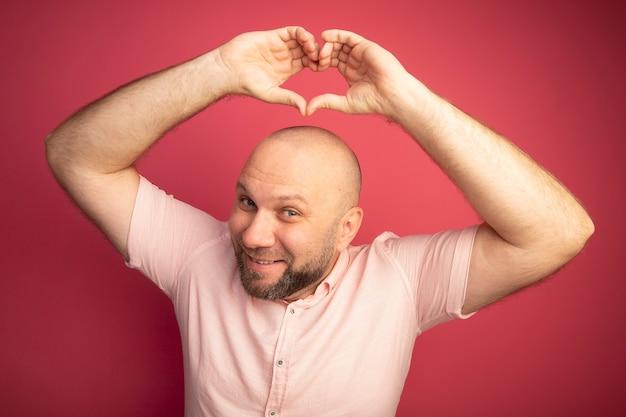 Glimlachende kale man van middelbare leeftijd met roze t-shirt die hartgebaar opheft dat op roze wordt geïsoleerd