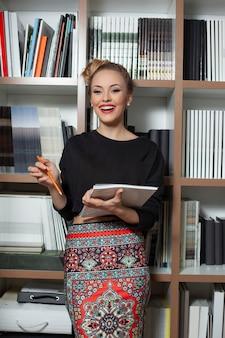 Glimlachende kantoormedewerker in kantoor met documenten in de hand, camera kijken