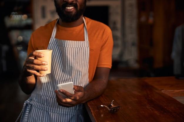 Glimlachende kapper die smartphone gebruikt en koffie drinkt op het werk