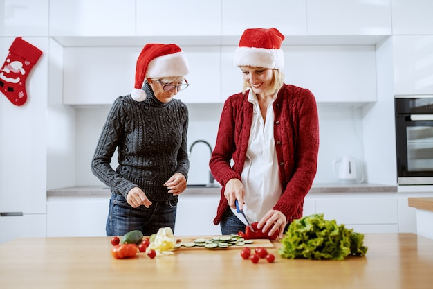 Glimlachende kaukasische blonde zwangere vrouw die gezonde maaltijd voor kerstmisdiner voorbereidt. naast haar staat haar moeder. beiden met kerstmutsen op het hoofd. keuken interieur.