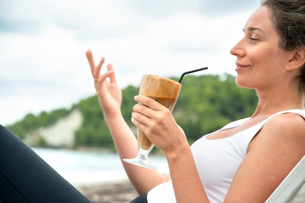 Glimlachende kaukasische de koffiedrank van de vrouwenholding op een strand met schuim en het drinken van stro met heuvels