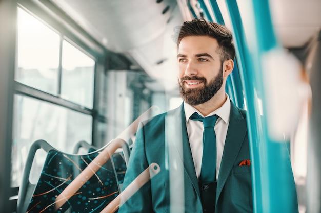 Glimlachende kaukasische gebaarde zakenman in turkooise kostuumzitting in openbare bus en het kijken via venster. goede energie is besmettelijk.