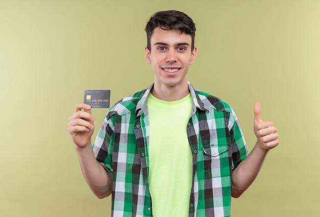 Glimlachende kaukasische jonge kerel die groen overhemd draagt dat creditcard zijn duim op geïsoleerde groene achtergrond houdt