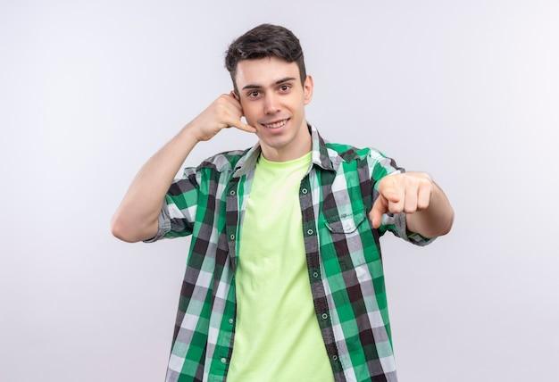 Glimlachende kaukasische jonge kerel die groen overhemd draagt dat oproepgebaar doet en u gebaar op geïsoleerde witte achtergrond toont