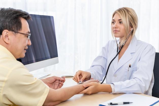 Glimlachende kaukasische vrouw arts die en een stethoscoop met pateint op het ziekenhuisruimte stellen dragen.