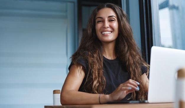 Glimlachende kaukasische vrouw die aan laptop werkt en gelukkig kijkt.