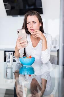 Glimlachende kaukasische vrouw die mobiele telefoon met behulp van terwijl verse groentensalade in keuken eet