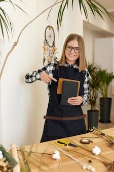 Glimlachende kaukasische vrouwelijke bloemist die notitieboekje in een winkel toont. bloemisterij.