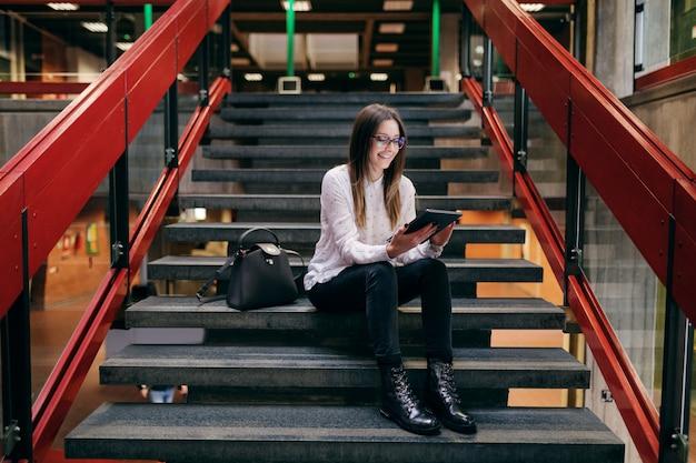 Glimlachende kaukasische vrouwelijke student met oogglazen en bruine haarzitting op de treden in de universiteitsbouw en het gebruiken van tablet