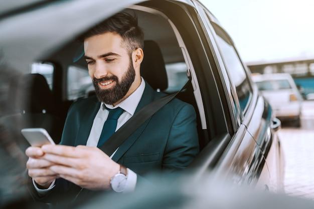 Glimlachende kaukasische zakenman in formele slijtage die slimme telefoon met behulp van terwijl het zitten in zijn auto op parkeerplaats.