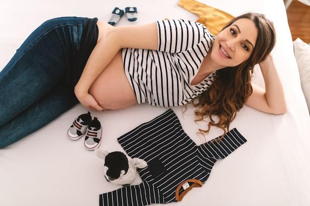Glimlachende kaukasische zwangere vrouw met lang bruin haar en in streepblouse die op bed in slaapkamer bepaalt. naast haar speelgoed en babykleertjes.