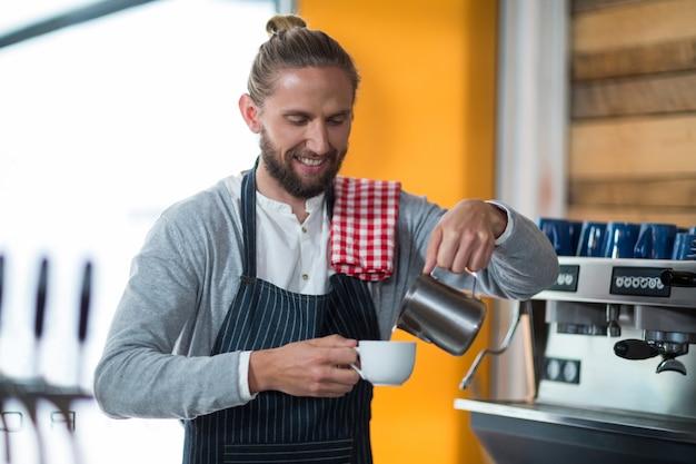 Glimlachende kelner die kop van koffie maakt bij teller