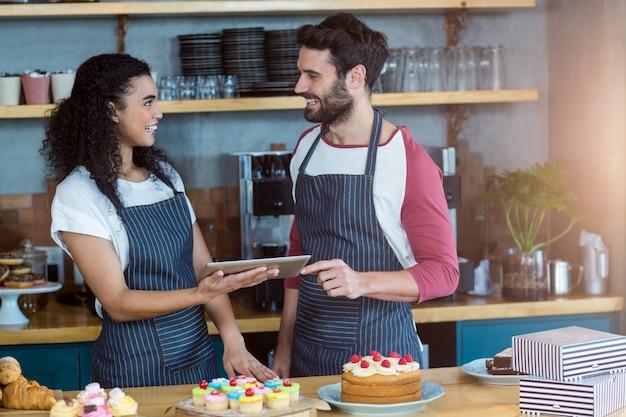 Glimlachende kelner en serveerster die digitale tablet gebruiken bij teller