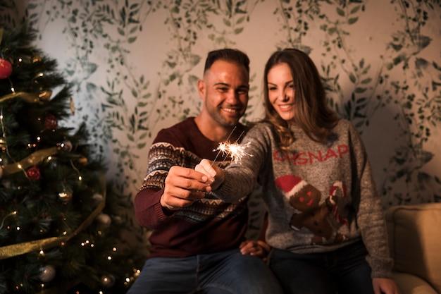 Glimlachende kerel dichtbij vrolijke dame met bengalen steekt dichtbij kerstboom aan
