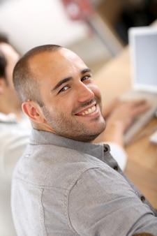 Glimlachende kerel in beroeps opleiding die vergadering bijwoont