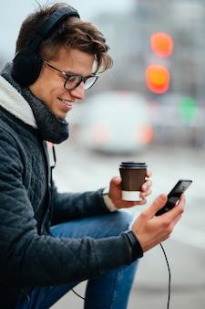 Glimlachende kerel in hoofdtelefoons, die zijn smartphone gebruiken, die een kop van hete koffie houden, in openlucht.