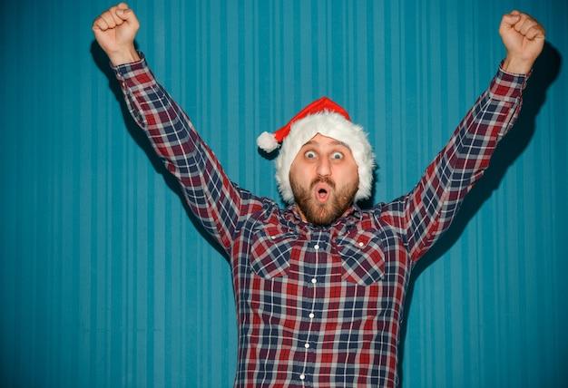 Glimlachende kerstmismens die een kerstmuts draagt op de blauwe studioachtergrond