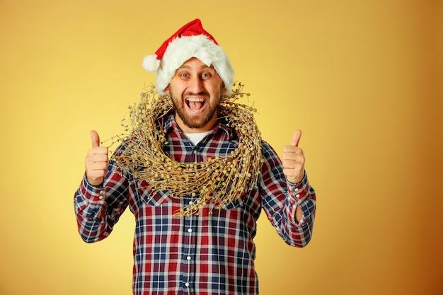 Glimlachende kerstmismens die een kerstmuts draagt op de oranje studioachtergrond