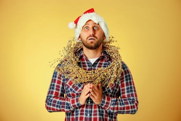 Glimlachende kerstmismens die een santahoed draagt die op oranje achtergrond bidt