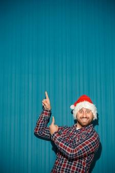 Glimlachende kerstmismens die een santahoed draagt