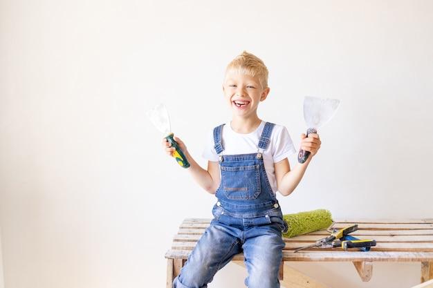 Glimlachende kindbouwer in een appartement met witte muren die bouwhulpmiddelen houden