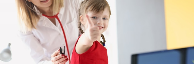 Glimlachende kinderarts arts luistert via stethoscoop naar ademhaling van de longen van kleine