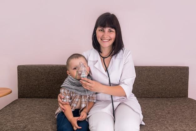 Glimlachende kinderarts die kleine jongen met vernevelaar helpt