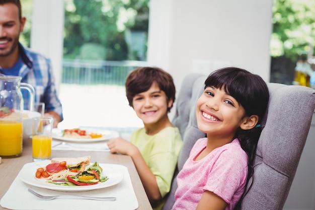 Glimlachende kinderen die bij eettafel zitten
