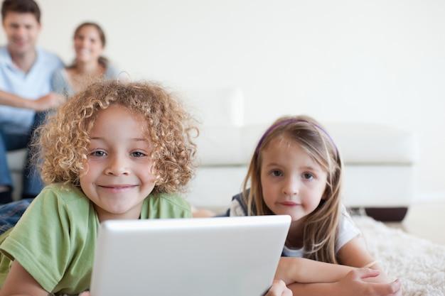 Glimlachende kinderen die een tabletcomputer met behulp van terwijl hun gelukkige ouders letten op