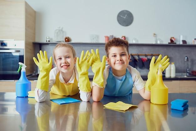 Glimlachende kinderen doen de schoonmaak in de keuken