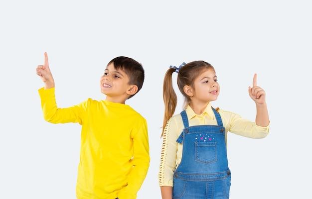 Glimlachende kinderen op een witte achtergrond wijzen naar de bovenkant van de lege ruimte.