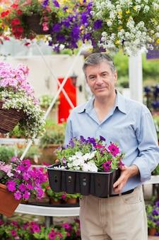 Glimlachende klant die bloemdozen buiten nemen