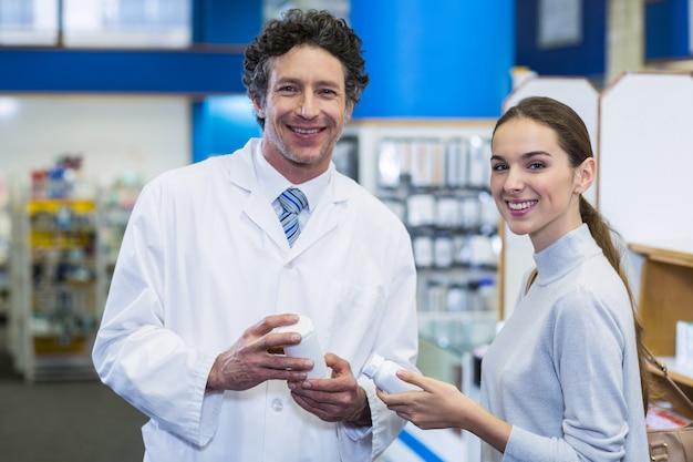 Glimlachende klant en apotheker de fles van de holdingsdrug in het ziekenhuis